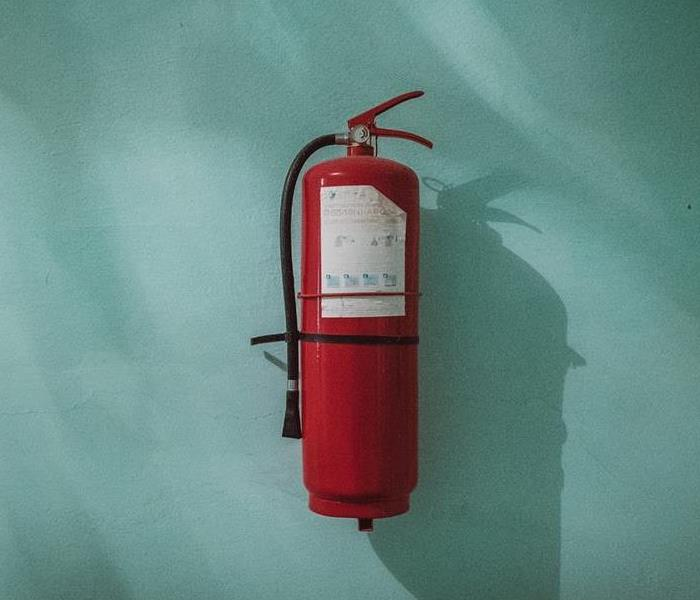 Fire extinguisher hung on a teal wall