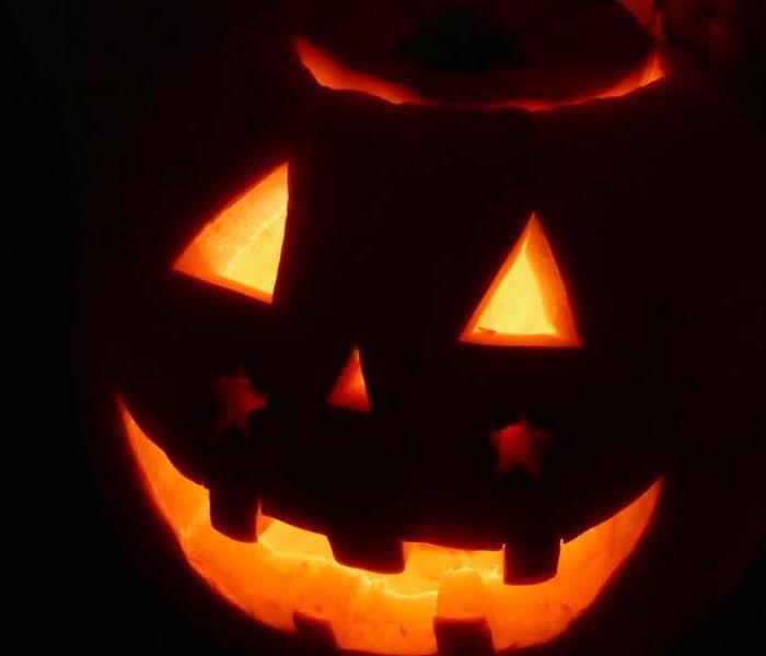 pumpkin glowing in the dark with triangle eyes and nose and a smile